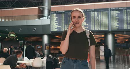 vliegticket : A young woman with a backpack standing at the airport  waiting departure talking on the phone