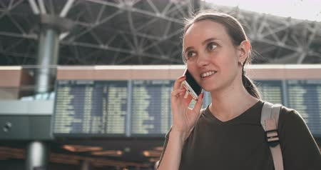 časová prodleva : Woman traveler talking on the phone at the airport and smiling Dostupné videozáznamy