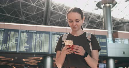 bilet : A woman looks at the screen of a mobile phone to find your e-ticket on the plane