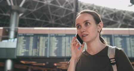 časová prodleva : A woman at the airport on the phone discussing the delay of his flight