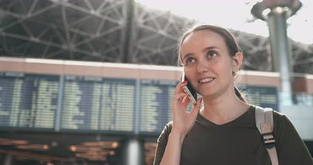 časová prodleva : Young beautiful woman standing at the airport calling on the phone