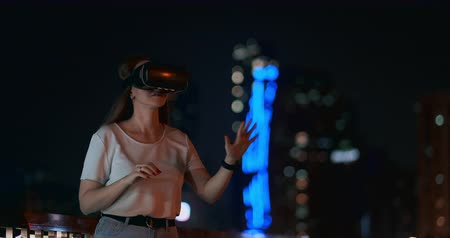 dvojitý : Young woman in VR glasses against of the night city