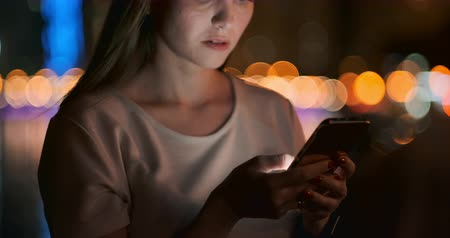 A young girl on the background of the night city looks into the smartphone screen