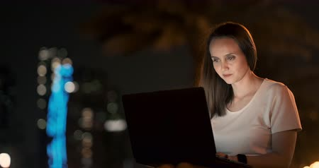 gyakornok : Woman developer sits in the Park at night in the city and writes code looking at the laptop screen Stock mozgókép