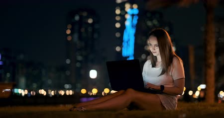 Young girl designer working remotely on laptop outside under palm trees at night
