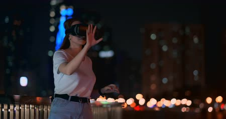 reaching : Young girl in virtual reality glasses in a big metropolis