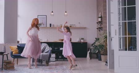puericultura : Cheerful mother little daughter standing in living room at home moving dancing to favourite song together. Child have fun with elder sister nanny or loving mother active leisure and lifestyle concept