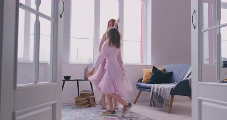 amigos : Active young mom babysiter and cute little kid daughter jumping dancing in modern house living room, happy family mother with child girl having fun enjoy playing funny activity together at home Stock Footage