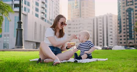 fiatal felnőttek : Young mom with baby sitting on the grass in the Park eating lunch
