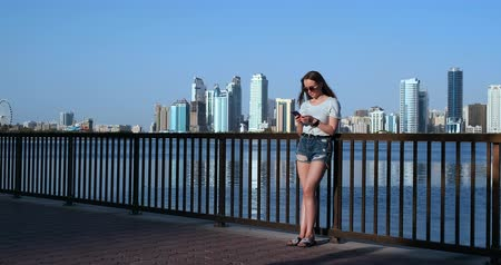 hírnök : Girl on the background of the big city and the Bay holding a smartphone in sunglasses