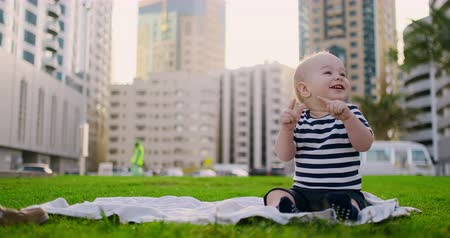 egyetlen virág : Happy small child sitting in grass with white daisies city background