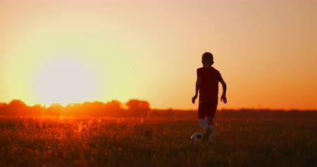 slintání : Tracking a boy football player running with a ball at sunset in the field