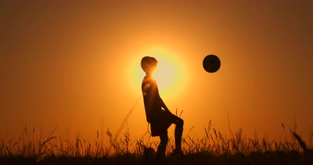 sertés : Little boy football player silhouette, practicing with the ball, the sunset Golden hour, slow motion.