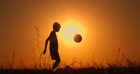 league : Little boy football player silhouette, practicing with the ball, the sunset Golden hour, slow motion.