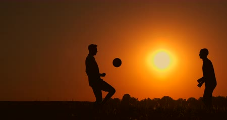 brothers : Two boys playing soccer at sunset. Silhouette of children playing with a ball at sunset. The concept of a happy family Stock Footage