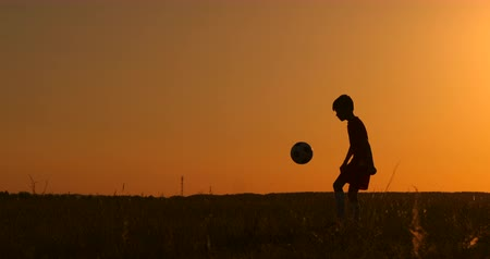 slintání : Silhouette of a boy playing football at sunset. A boy juggles a ball in the field at sunset
