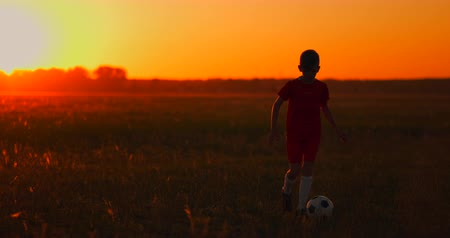 slintání : A boy with a football runs to the camera at sunset