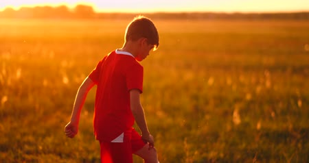 piłkarz : Boy football player at sunset juggling the ball in the field
