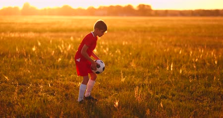 piłkarz : Young boy football player at sunset juggling with the ball in the field Wideo