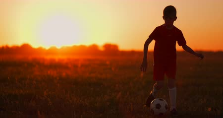 top sürme : A boy with a football runs to the camera at sunset