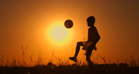 brazilian : Silhouette of a boy playing football at sunset. A boy juggles a ball in the field at sunset