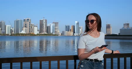 dubaj : A girl with long hair dials a message on the smartphone at the quay of Dubai. Dostupné videozáznamy