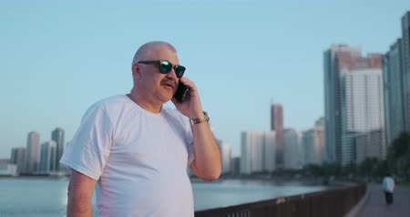 söylemek : Senior man standing on the waterfront in the summer talking on the phone Stok Video