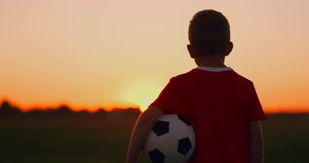 jogador de futebol : Young football player goes with the ball on the field dreaming of a football career, at sunset looking at the sun
