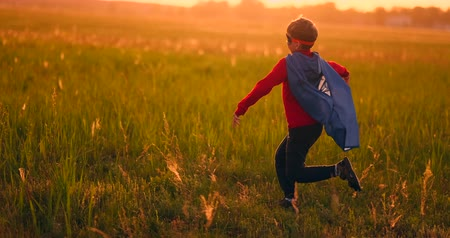 megmentő : A boy in a suit and a superhero mask running across the field at sunset on the grass