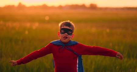спаситель : A boy in a suit and a superhero mask running across the field at sunset on the grass