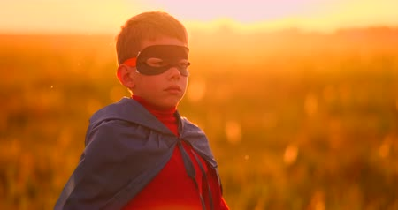 герои : A child in the costume of a superhero in a red cloak runs across the green lawn against the backdrop of a sunset toward the camera Стоковые видеозаписи