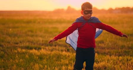 fingir : Boy in superhero costume and mask running across the field at sunset dreaming and fantasizing