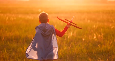 kask : The boy runs across the field with a plane in his hands at sunset