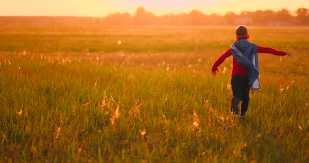 předstírat : Little superhero boy in the field at sunset fantasizes and dreams