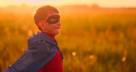 umutlu : The boy in the mask and Cape of a super hero at sunset in a field Stok Video
