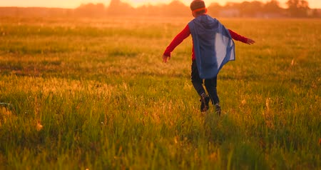 stripboek : Boy in superhero costume and mask running across the field at sunset dreaming and fantasizing