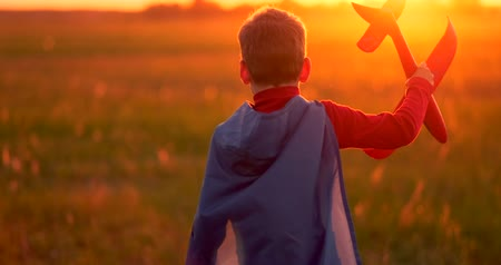 оригами : The boy presents himself as a pilot and runs into the field at sunset with a plane
