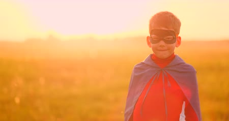 hopeful : Portrait of a boy in a mask of a super hero looking at the camera standing in a field at sunset.