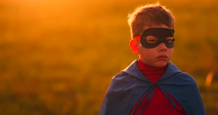 герои : The boy in the mask and Cape of a super hero at sunset in a field Стоковые видеозаписи