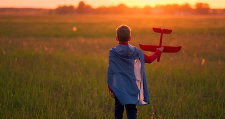 оригами : Boy playing in the field with a plane in his hands at sunset