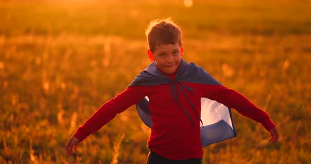 plášť : A child in the costume of a superhero in a red cloak runs across the green lawn against the backdrop of a sunset toward the camera Dostupné videozáznamy