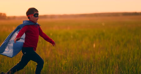 stripboek : A boy in a suit and a superhero mask running across the field at sunset on the grass