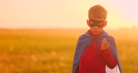 герои : Portrait of a boy in a mask of a super hero looking at the camera standing in a field at sunset.