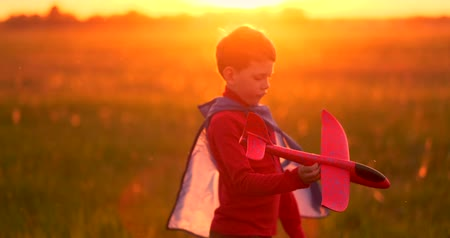 letec : The boy runs across the field with a plane in his hands at sunset
