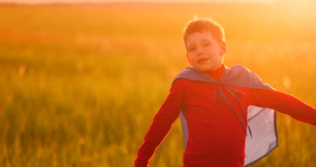 кулак : Little boy plays and dreams of a super hero at sunset