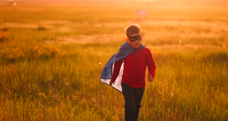 герой : A boy in a suit and a superhero mask running across the field at sunset on the grass