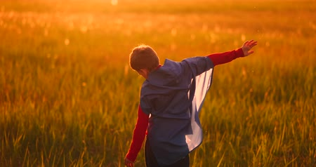 předstírat : Little superhero boy in the field at sunset fantasizes and dreams.