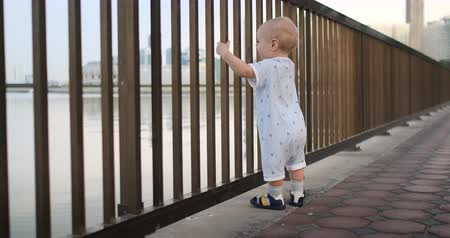 otcovství : Dancing cheerful European boy near the fence keeps ha railing and dancing standing and looking at the view of the promenade in the summer in the UAE Dostupné videozáznamy