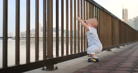 conserva : Dancing cheerful European boy near the fence keeps ha railing and dancing standing and looking at the view of the promenade in the summer in the UAE Stock Footage
