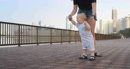 french street : Smiling Boy holding his mothers hand makes the first steps walking along the promenade in the summer